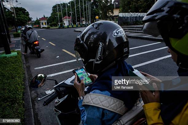 Motorcyclists Nadia and Tiara play Pokemon Go game on their smartphones on July 24 2016 in Yogyakarta Indonesia Pokemon Go which uses Google Maps and...