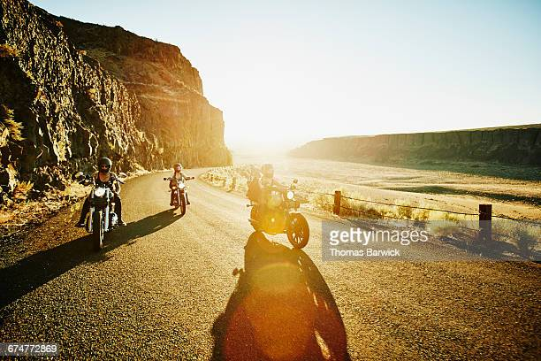 Motorcyclists on road trip through desert canyon