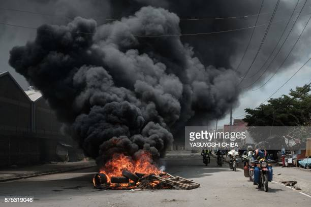 TOPSHOT Motorcyclists pass a burning tyre barricade following a demonstration by Kenyan opposition party National Super Alliance supporters on...