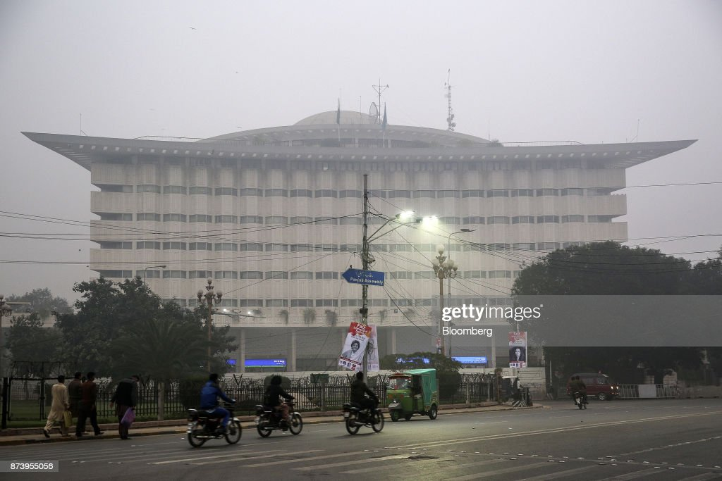 Motorcyclists pass the Water and Power Development Authority building shrouded in smog in Lahore Pakistan on Tuesday Nov 14 2017 The fates of 15...