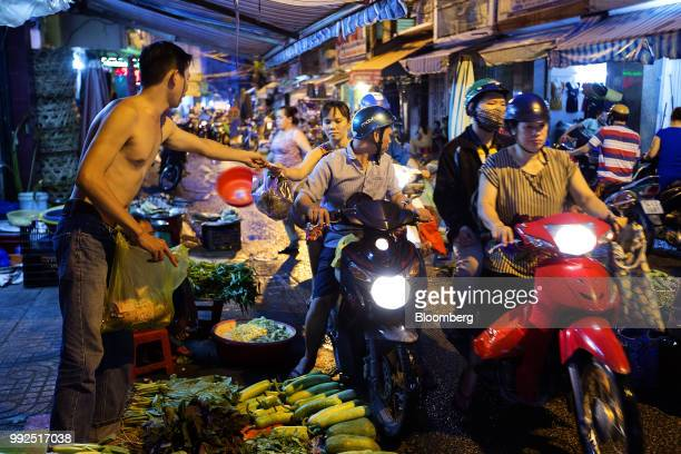 Motorcyclists pass vendors selling food in a market at night in Ho Chi Minh City Vietnam on Wednesday June 20 2018 For decades Vietnamese have...
