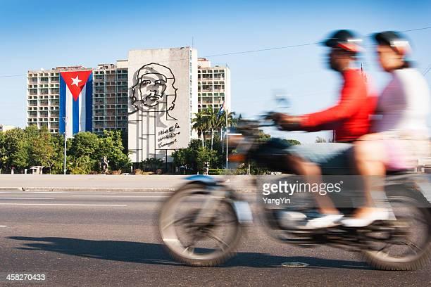 motorcyclists passing che guevara image, ministry of interior building, havana - plaza de la revolución havana stock photos and pictures