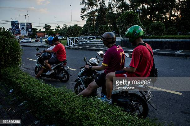 Motorcyclists play Pokemon Go game on their smartphones on July 24 2016 in Yogyakarta Indonesia 'Pokemon Go' which uses Google Maps and a smartphone...