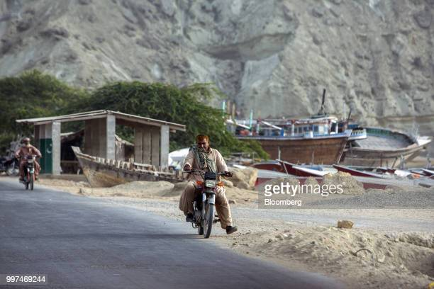 Motorcyclists ride along a road past fishing boats on Marine Drive in Gwadar Balochistan Pakistan on Tuesday July 4 2018 What used to be a small...