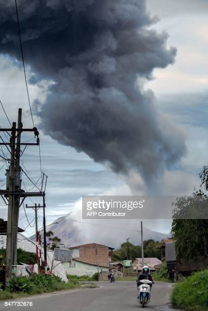 Motorcyclists ride as Mount Sinabung volcano spews ash as seen from Tangkulen village in Karo North Sumatra province on September 16 2017 Sinabung...