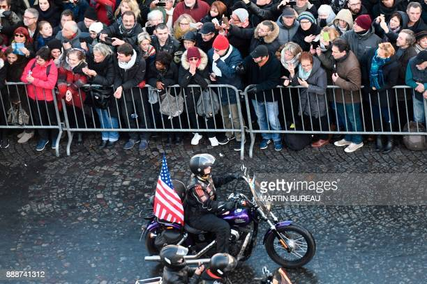 Motorcyclists ride down the ChampsElysees avenue during a 'popular homage' to late French singer Johnny Hallyday on December 9 2017 in Paris French...