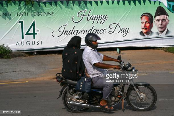 Motorcyclists ride past a banner reading 'Happy Independence Day' with images of founder leader Mohammad Ali Jinnah and national poet Allama Mohammad...