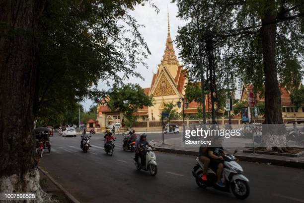 Motorcyclists ride past a temple in Phnom Penh Cambodia on Sunday July 29 2018 Cambodian Prime MinisterHun Senextended his morethanthreedecade run...