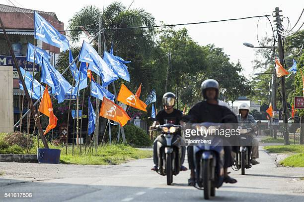 Motorcyclists ride past campaign flags for the National Trust party and the Barisan Nasional party in Sungai Besar Selangor Malaysia on Thursday June...