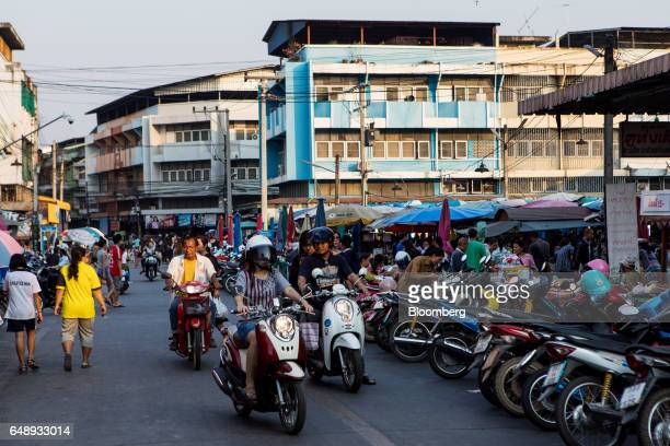 Motorcyclists ride past street food stalls and parked vehicles in Nan Nan Province Thailand on Friday March 3 2017 After more than a year of...