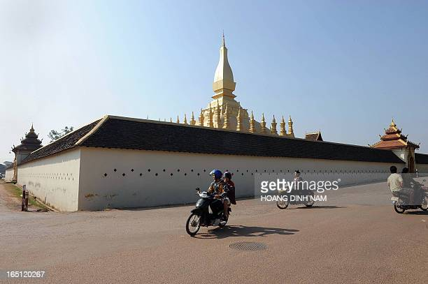 Motorcyclists ride past That Luang temple the symbole of Laos in downtown Vientiane on December 9 2009 Laos a landlock communist nation is hosting...