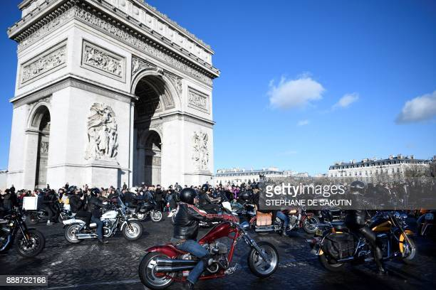 Motorcyclists ride past the Arc de Triomphe on the Place Charles de Gaulle square during a 'popular homage' to late French singer Johnny Hallyday on...