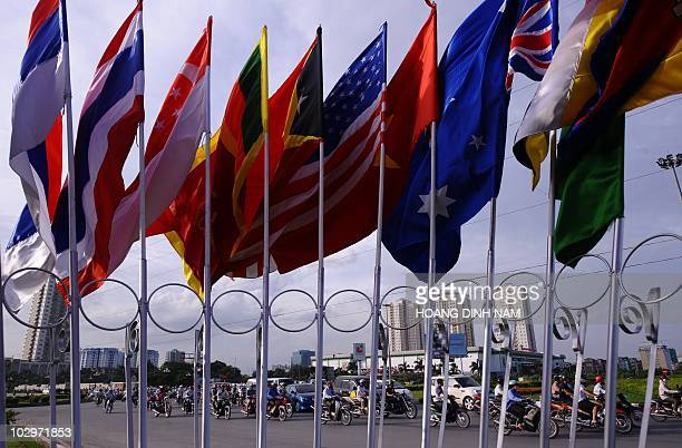 Motorcyclists ride past the flags of participating countries of the ministerial meeting of the Association of Southeast Asian Nations in Hanoi on...