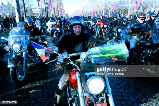 Motorcyclists ride their bikes during a 'popular homage' to late French singer Johnny Hallyday as his coffin is driven down the ChampsElysees avenue...