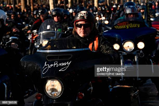 Motorcyclists ride their bikes during a 'popular homage' to late French singer Johnny Hallyday on the ChampsElysees avenue on December 9 2017 in...