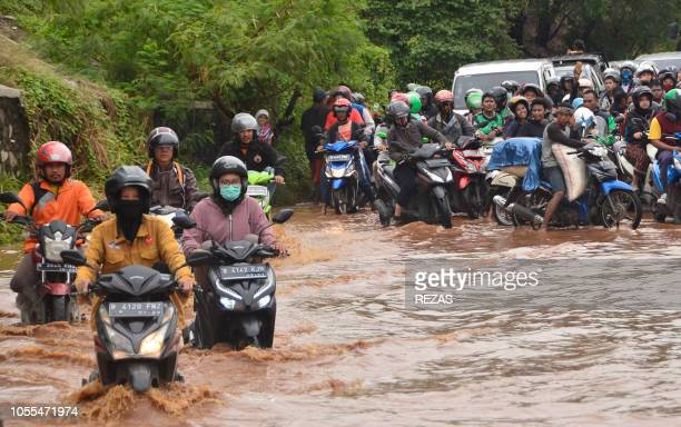 Motorcyclists ride through floodwaters in Bekasi West Java province on October 30 following heavy monsoon rains in the area