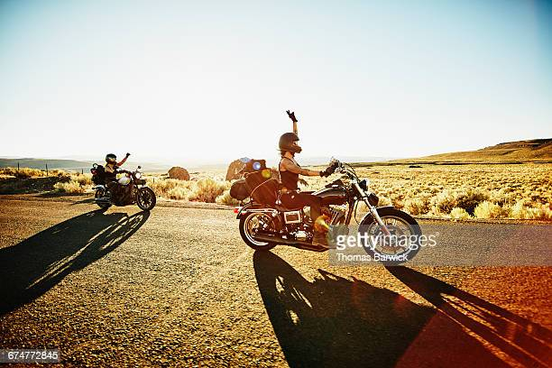 Motorcyclists riding on road with arms raised