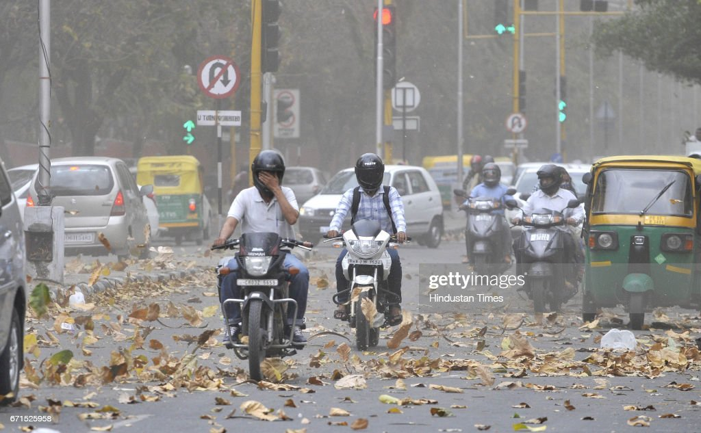 Motorcyclists riding through the dust storm and strong winds on April 22 2017 in Chandigarh India The storm led to trees falling in some areas power..