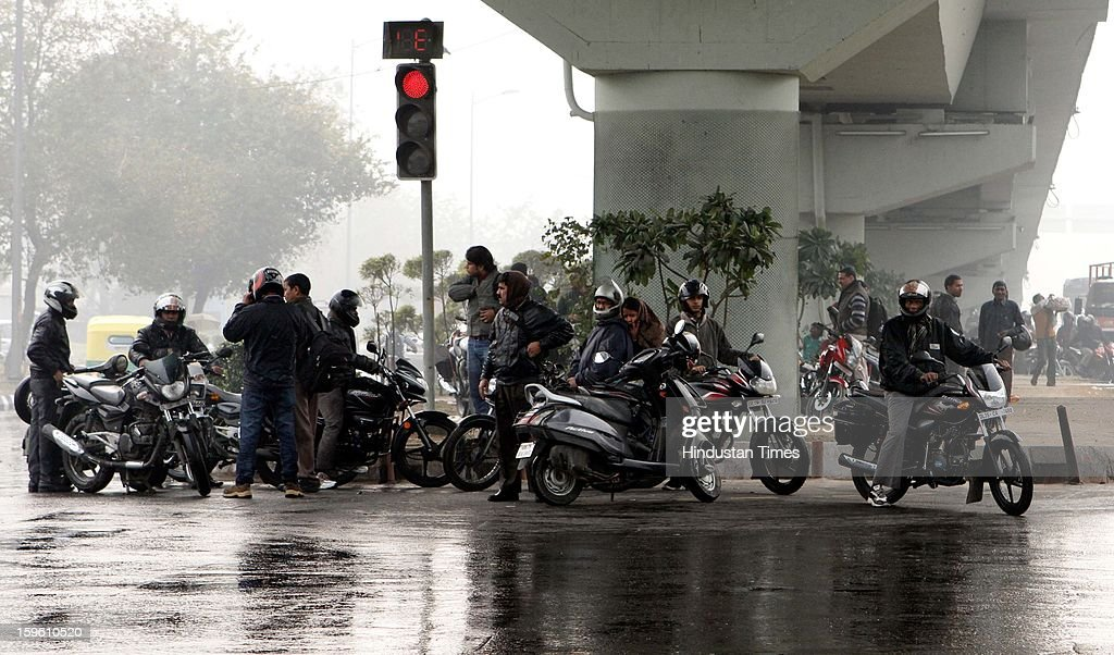 Motorcyclists take shelter under a flyover during sudden rain at NH 24 - Ring Road T-point on January 17, 2013 in New Delhi, India. Capital witnessed light rain and chilly winds even though temperatures were above average.