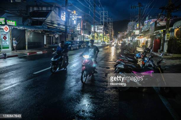 Motorcyclists travel along a near-empty road in Patong, Phuket, Thailand, on Saturday, Dec. 19, 2020. The tepid response to Thailands highly...