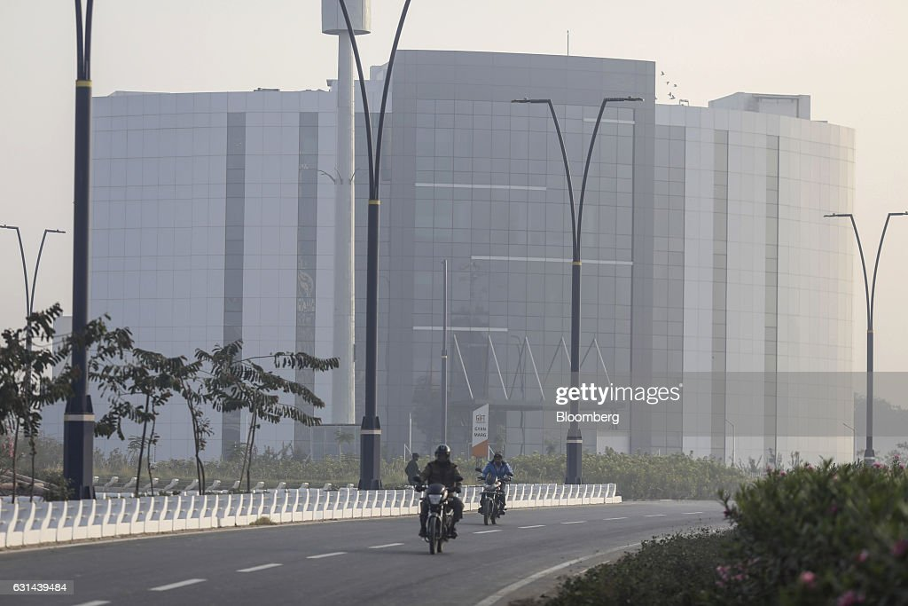 General views of the under construction tec city motorcyclists travel along a road near a commercial building in gujarat international finance tec city negle Gallery