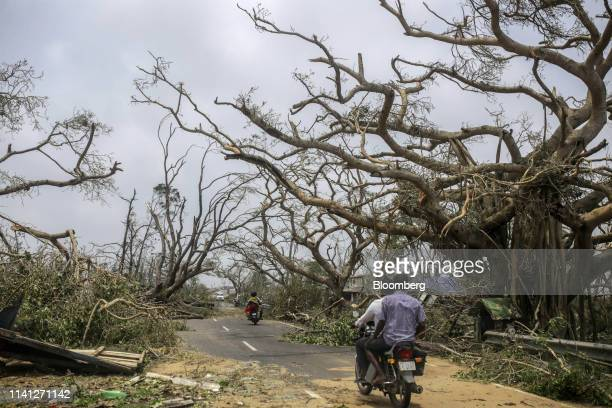 Motorcyclists travel past damaged trees after Cyclone Fani passes in the Puri district of Odisha India on Saturday May 4 2019 A category 4 storm with...