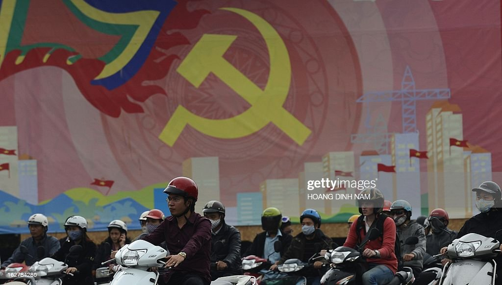 Motorcyclists wait for a green light next to a communist propaganda poster in downtown Hanoi on February 27, 2013. A Vietnamese journalist has been fired from his state-run newspaper after criticising the head of the ruling Communist Party in a personal blog. Nguyen Dac Kien was sacked from the Family and Society newspaper less than 24 hours after he published an essay on his blog -- which quickly went viral -- criticising a speech by the party's general secretary Nguyen Phu Trong. AFP PHOTO/HOANG DINH Nam