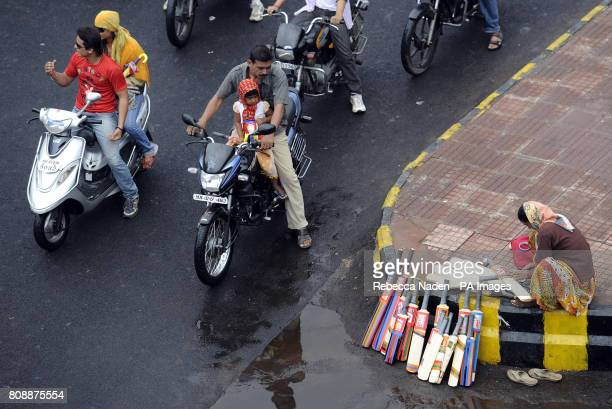 Motorcyclists watch a street seller of cricket bats in Nagpur city centre India