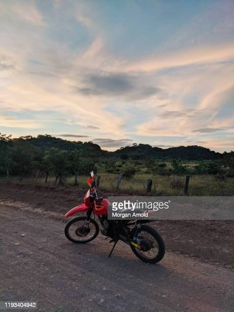 motorcyle on a rural dirt road - motorsport stock pictures, royalty-free photos & images