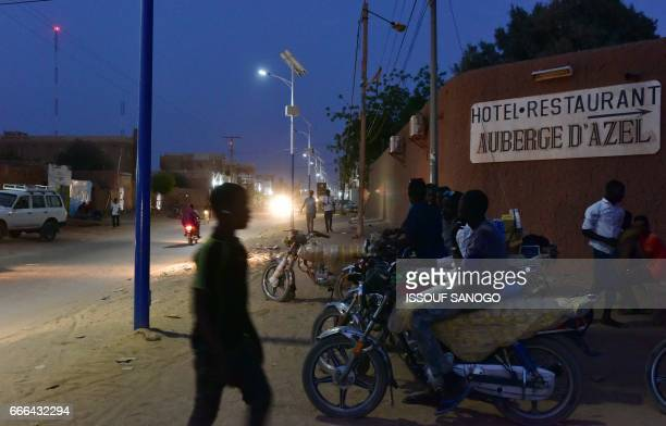 Motorcyle taxi riders wait for customers outside the gates of a hotel in Agadez northern Niger on April 5 2017 Agadez the gateway to the desert a...