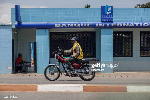 A motorcylist taxi driver passes by the front of a Bicec bank branch operated by Groupe BPCE in Kribi Cameroon on Thursday Aug 2 2018 Since the...