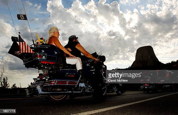 Motorcylists approach Devils Tower National Monument WY background which is one of many popular destinations for cyclists attending the 61st annual...