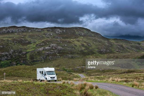 Motorhome / campervan driving along winding single track road with passing places in the Scottish Highlands, Ross-shire, Scotland, UK.
