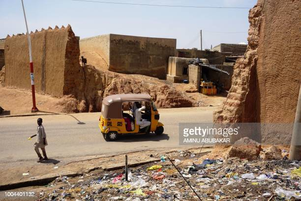 Motorised rickshaw drives on a road that runs through a demolished section of Kano's ancient city wall in Kano, Nigeria, on June 12, 2018. The wall...