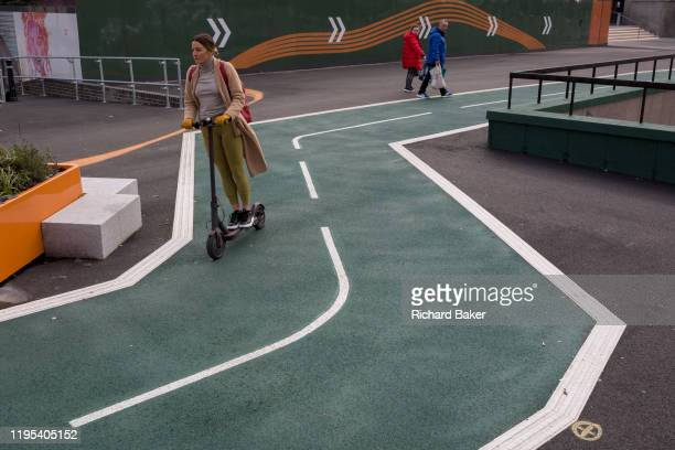 Motorised scooter lady takes the shortest route through the bends of a new cycling path, a regenerated landscape created outside Croydon College and...