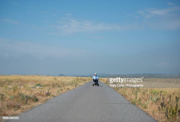 motorised wheelchair on path - mobility scooter stock photos and pictures