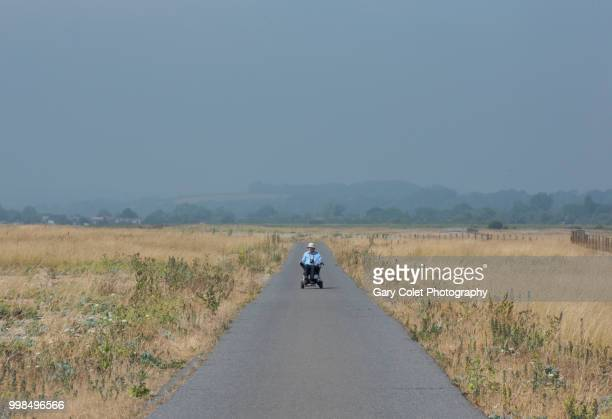 motorised wheelchair on path - gary colet stock pictures, royalty-free photos & images