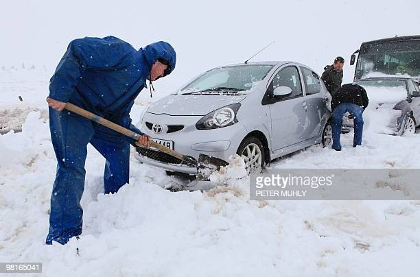 A motorist digs his car out from heavy snow on the Glenshane pass near Londonderry Northern Ireland on March 31 2010 About 300 people were rescued...
