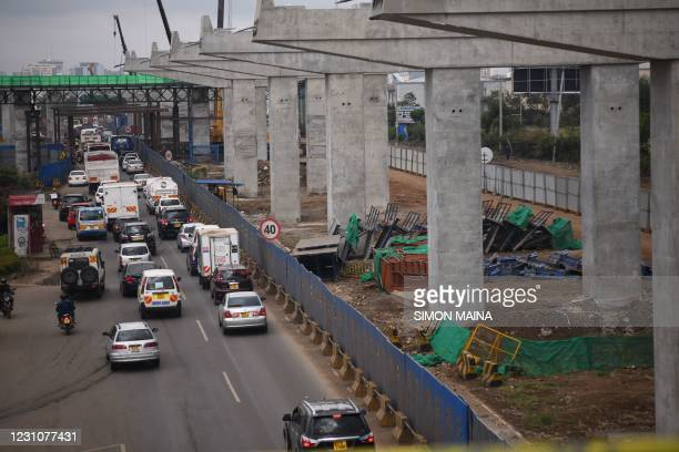 Motorist drive on Mombasa road, next to the ongoing construction site of the Nairobi Expressway, undertaken by the Chinese contractor China Road and...