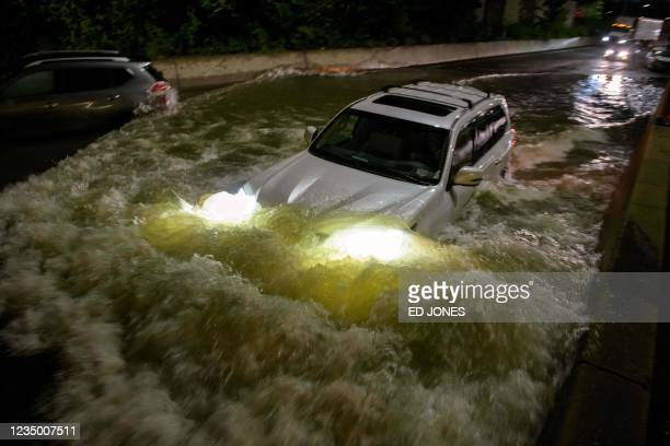 Motorist drives a car through a flooded expressway in Brooklyn, New York early on September 2 as flash flooding and record-breaking rainfall brought...