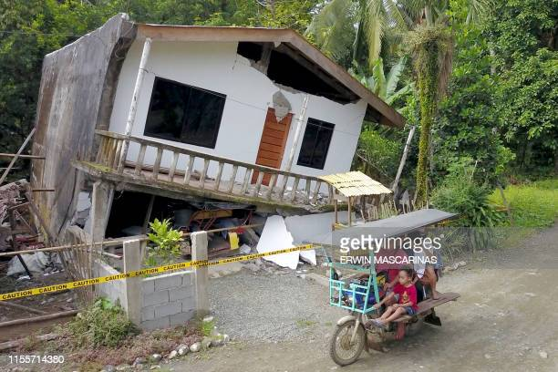Motorist drives past a destroyed house after a large earthquake that hit Surigao City, in southern island of Mindanao on July 15, 2019. - Fifty-one...