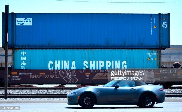 A motorist drives past shipping containers including one from China Shipping a shipping conglomerate under direct administration of China's State...