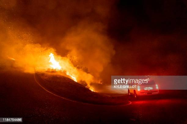 A motorist drives through flames on Painted Cave Road as the Cave fire burns a hillside in Santa Barbara California on November 26 2019 The...