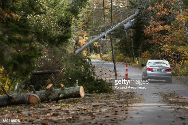 A motorist drives under a utility pole propped up by a pine tree limb on High Head Road in Harpswell on Wednesday November 1 2017 The Harpswell...