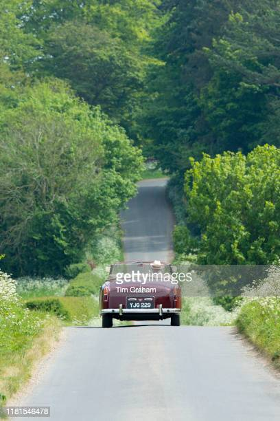 Motorist driving away in a British made Alvis TD21 classic car along a country lane in The Cotswolds, England.