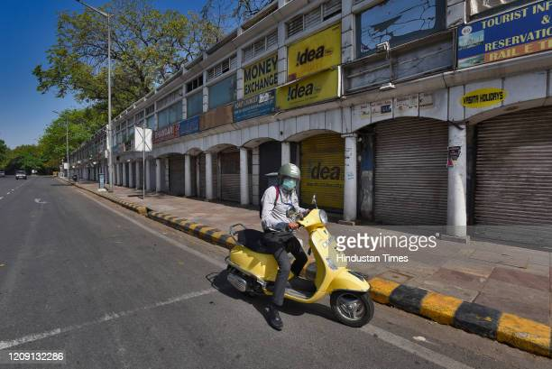 A motorist is seen next to closed shops on day eleven of the 21day nationwide lockdown to curb the spread of coronavirus at Connaught Place on April...
