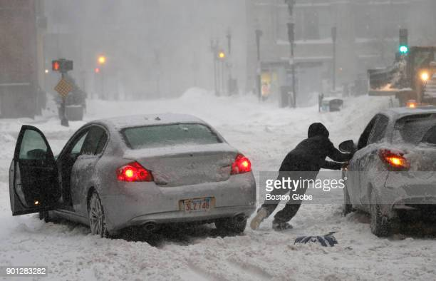A motorist leaves his car to aid another stuck on State Street in downtown Boston during blizzard conditions in Boston MA on Jan 04 2018