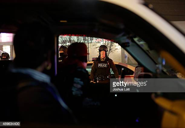A motorist protesting the shooting death of Michael Brown confront police officers in riot gear November 26 2014 in Ferguson Missouri Brown a...