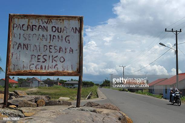 A motorist rides past a board that reads 'If you date on the beach the risk is on your own' in Banda Aceh on October 22 2015 Gay people caught having...