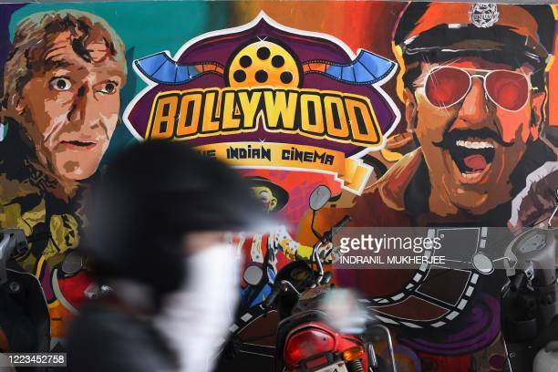 A motorist rides past a wall mural with images of Bollywood actors in Mumbai on June 29 2020 Bollywood will resume film shoots immediately industry...